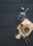 Σύνολο ορεκτικών κρασιού Ποτήρι του κόκκινου κρασιού, του γαλλικών λουκάνικου και των ελιών στο μαύρο ξύλινο σκηνικό Στοκ φωτογραφία με δικαίωμα ελεύθερης χρήσης