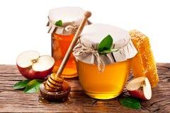 Σύνολο δοχείων γυαλιού του μελιού, μήλα, κυψελωτός παλαιός ξύλινος πίνακας φ Στοκ Εικόνες