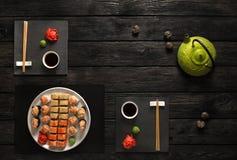 Σύνολο σουσιών και ρόλων με teapot στη μαύρη αγροτική ξύλινη, τοπ άποψη Στοκ φωτογραφία με δικαίωμα ελεύθερης χρήσης