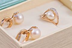 Σύνολο χρυσών σκουλαρικιών και δαχτυλιδιών με τα μαργαριτάρια Στοκ Φωτογραφίες