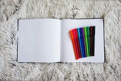 Σύνολο χρωματισμένων μανδρών και ενός σημειωματάριου στο κρεβάτι Στοκ Φωτογραφίες