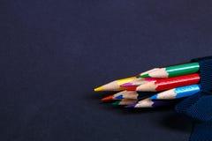 Σύνολο χρωματισμένων μολυβιών που τυλίγονται σε μια μπλε κορδέλλα στο μαύρο υπόβαθρο πίσω σχολείο διάστημα αντιγράφων Στοκ εικόνα με δικαίωμα ελεύθερης χρήσης