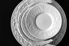 Σύνολο όμορφων άσπρων κεραμικών πιάτων ανακούφισης γευμάτων στο μαύρο υπόβαθρο στοκ φωτογραφία