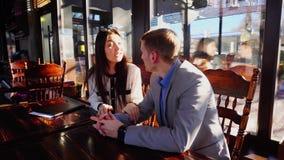 Σύντροφοι ομάδας που χρονολογούν στον καφέ και το αγκάλιασμα φιλμ μικρού μήκους