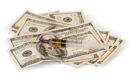 Σύριγγα για την έγχυση με το φάρμακο και δολάρια που απομονώνονται στο λευκό Στοκ Εικόνες
