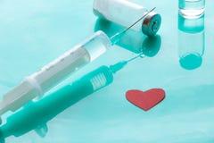 Σύριγγα, ιατρική, κόκκινο σύμβολο καρδιών σε ένα πράσινο υπόβαθρο Στοκ εικόνα με δικαίωμα ελεύθερης χρήσης