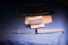 Σύριγγα και βελόνα, γάζες και χειρουργικά όργανα στον πίνακα στοκ εικόνες