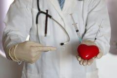 Σύριγγα στο χέρι γιατρών καρδιών Στοκ Φωτογραφίες