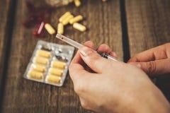Σύριγγα χεριών γυναικών με το φάρμακο στοκ εικόνα με δικαίωμα ελεύθερης χρήσης
