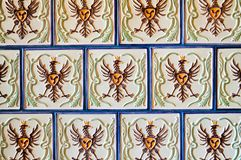 Σύσταση ένα όμορφο τετραγωνικό άσπρο κεραμικό κεραμίδι με τα σχέδια υπό μορφή πουλιού, αετός, κόκκορας με τις μπλε ραφές εθνικό v στοκ φωτογραφία