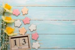 Σύσταση ενός δέντρου με τα κίτρινα λουλούδια και τα σπιτικά μπισκότα υπό μορφή μήνα με ένα ημερολόγιο στο οποίο στις 13 Μαΐου, ο  στοκ εικόνες με δικαίωμα ελεύθερης χρήσης