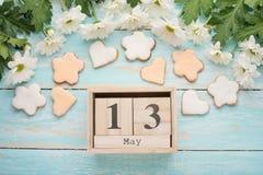 Σύσταση ενός δέντρου με τα κίτρινα λουλούδια και τα σπιτικά μπισκότα υπό μορφή μήνα με ένα ημερολόγιο στο οποίο στις 13 Μαΐου, ο  στοκ φωτογραφίες με δικαίωμα ελεύθερης χρήσης