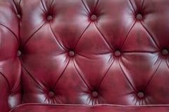 Σύσταση κινηματογραφήσεων σε πρώτο πλάνο του εκλεκτής ποιότητας κόκκινου καναπέ δέρματος για το υπόβαθρο Στοκ Εικόνα
