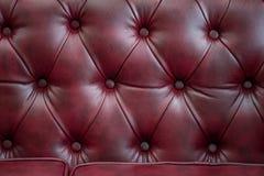 Σύσταση κινηματογραφήσεων σε πρώτο πλάνο του εκλεκτής ποιότητας κόκκινου καναπέ δέρματος για το υπόβαθρο Στοκ Φωτογραφίες