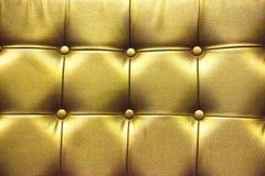 Σύσταση κινηματογραφήσεων σε πρώτο πλάνο του εκλεκτής ποιότητας χρυσού καναπέ δέρματος για το υπόβαθρο Στοκ Εικόνες