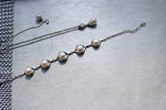 Σύσταση με το κόσμημα μαργαριταριών, μαργαριτάρια, ασημένιες αλυσίδες, κρύσταλλα των πολύτιμων λίθων, διαμάντια, διαμάντια σε ένα Στοκ Φωτογραφία