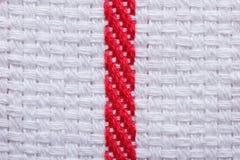 Σύσταση της άσπρης πετσέτας κουζινών βαμβακιού με ένα κόκκινο λωρίδα. Μακροεντολή. Στοκ εικόνες με δικαίωμα ελεύθερης χρήσης