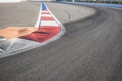 Σύσταση της ασφάλτου φυλών μηχανών και της κόκκινης άσπρης συγκράτησης Κλείστε επάνω στο κύκλωμα οδών Grand Prix στοκ εικόνα