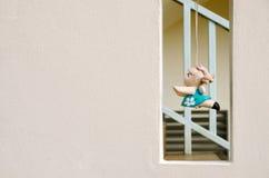 Σύσταση τοίχων με την τετραγωνική κενή και κρεμώντας κούκλα αργίλου Στοκ Εικόνες