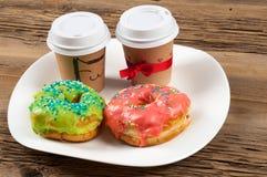 Σύσταση, υπόβαθρο, δύο donuts και καφές Donuts που καλύπτεται με Στοκ Φωτογραφίες