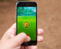 Σύλληψη ενός Pokemon ενώ το παιχνίδι Pokemon πηγαίνει Στοκ Φωτογραφίες