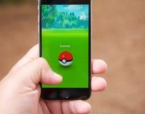 Σύλληψη ενός Pokemon ενώ το παιχνίδι Pokemon πηγαίνει Στοκ Εικόνα
