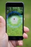 Σύλληψη ενός Pokemon ενώ το παιχνίδι Pokemon πηγαίνει Στοκ εικόνες με δικαίωμα ελεύθερης χρήσης