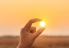 Σύλληψη του ήλιου στο ηλιοβασίλεμα στα δάχτυλα Στοκ εικόνες με δικαίωμα ελεύθερης χρήσης