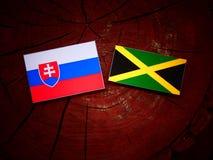 Σλοβάκικη σημαία με την τζαμαϊκανή σημαία σε ένα κολόβωμα δέντρων Στοκ Εικόνες