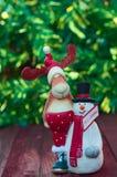 Τάρανδος Χριστουγέννων με το παιχνίδι χιονανθρώπων στο θολωμένο πράσινο υπόβαθρο Στοκ Φωτογραφία
