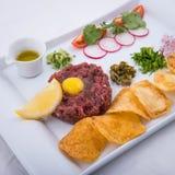 Τάρταρος βόειου κρέατος με τα τσιπ πατατών και το ελαιόλαδο στοκ εικόνα με δικαίωμα ελεύθερης χρήσης