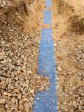 Τάφρος με την μπλε πλαστική ταινία προστασίας Χαρακτηρισμένος των καλωδίων κάτω από τον άργιλο κατά τη διάρκεια του κτηρίου Διαδι Στοκ Εικόνες