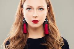 Τέλεια γυναίκα με τα κόκκινα χείλια Makeup και τα σκουλαρίκια κοσμήματος Στοκ φωτογραφία με δικαίωμα ελεύθερης χρήσης