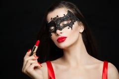 Τέλεια γυναίκα στη μάσκα καρναβαλιού με το κόκκινο κραγιόν στοκ εικόνα