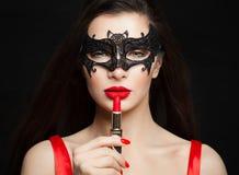 Τέλεια γυναίκα brunette με τα κόκκινα χείλια στη μαύρη μάσκα καρναβαλιού Makeup και έννοια καλλυντικών στοκ φωτογραφίες