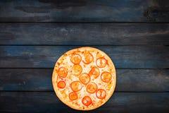 Τέλεια πίτσα Μαργαρίτα με τις φέτες ντοματών σε ένα σκοτεινό ξύλινο υπόβαθρο Τοπ κατώτατος προσανατολισμός άποψης Στοκ Εικόνες
