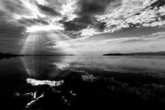 Τέλεια συμμετρική και θεαματική άποψη μιας λίμνης, με τα σύννεφα, τις ακτίνες ουρανού και ήλιων που απεικονίζουν στο νερό Στοκ Φωτογραφίες