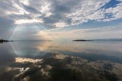 Τέλεια συμμετρική και θεαματική άποψη μιας λίμνης, με τα σύννεφα, τις ακτίνες ουρανού και ήλιων που απεικονίζουν στο νερό Στοκ Εικόνα