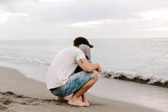 Τέλειοι νέοι πατέρας Adorably και οικογένεια γιων μικρών παιδιών μωρών που έχει το χρόνο διασκέδασης στην αμμώδη παραλία κατά τη  στοκ φωτογραφία