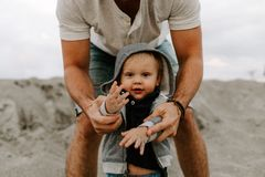 Τέλειοι νέοι πατέρας Adorably και οικογένεια γιων μικρών παιδιών μωρών που έχει το χρόνο διασκέδασης στην αμμώδη παραλία κατά τη  στοκ φωτογραφίες