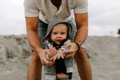 Τέλειοι νέοι πατέρας Adorably και οικογένεια γιων μικρών παιδιών μωρών που έχει το χρόνο διασκέδασης στην αμμώδη παραλία κατά τη  στοκ εικόνες