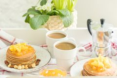 Τέλειο πρόγευμα για 2 Δίσκος με τις τηγανίτες με την πορτοκαλιά μαρμελάδα και τα καρύδια σε εκλεκτής ποιότητας πιάτα και 2 άσπρα  Στοκ φωτογραφία με δικαίωμα ελεύθερης χρήσης