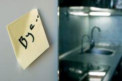 Τέλος της έννοιας σχέσης: αντίο σημειώστε σε ένα ψυγείο με τις συσκευές κουζινών και τα κρύα φω'τα στο θολωμένο υπόβαθρο στοκ εικόνες