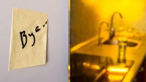 Τέλος της έννοιας σχέσης: αντίο σημειώστε σε ένα ψυγείο με τις συσκευές κουζινών και τα κίτρινα φω'τα στο θολωμένο υπόβαθρο στοκ εικόνες