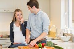 Τέμνοντα λαχανικά ατόμων για την έγκυο σύζυγό του Στοκ εικόνα με δικαίωμα ελεύθερης χρήσης