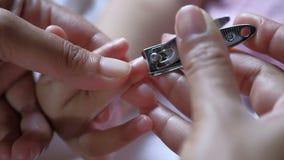 Τέμνοντα καρφιά μητέρων με το ψαλίδι στο μωρό απόθεμα βίντεο