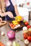 Τέμνοντα λαχανικά κοριτσιών για τη σαλάτα σε ένα ξύλινο γραφείο στο δωμάτιο κουζινών τρόφιμα έννοιας υγιή Στοκ Εικόνα