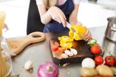 Τέμνοντα λαχανικά κοριτσιών για τη σαλάτα σε ένα ξύλινο γραφείο στο δωμάτιο κουζινών τρόφιμα έννοιας υγιή Στοκ Εικόνες