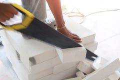 Τέμνοντα τούβλα εργαζομένων με το πριόνι crosscut στοκ εικόνες