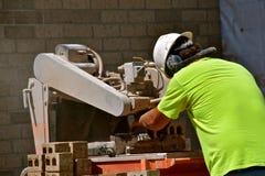 Τέμνοντα τούβλα εργατών οικοδομών στο πριόνι στοκ φωτογραφίες